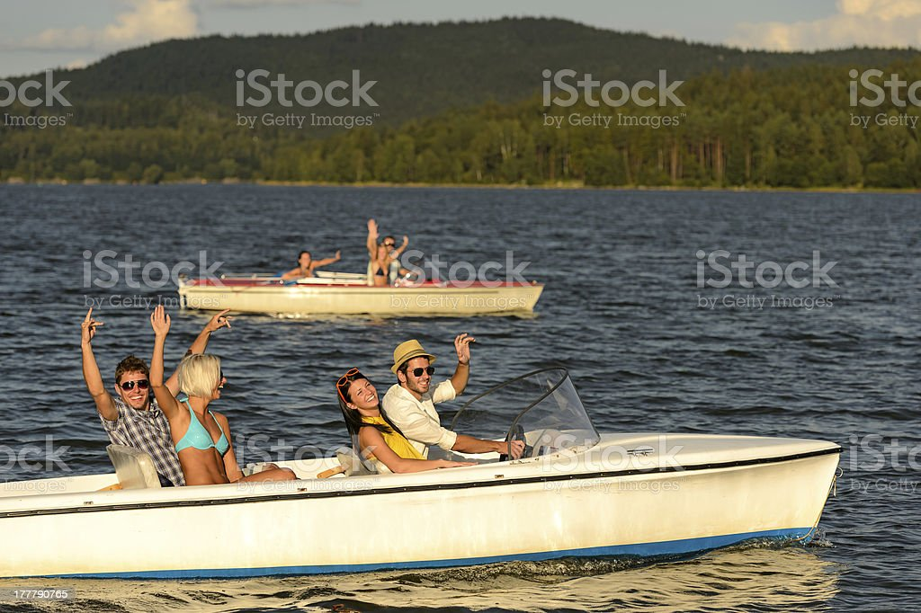 Group of friends racing with motorboats royalty-free stock photo