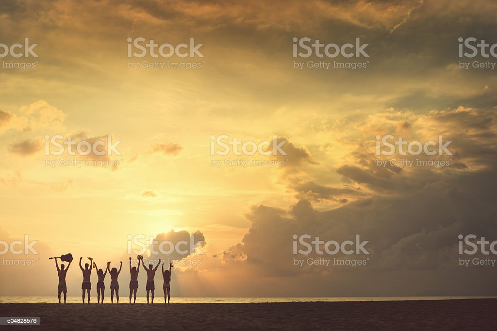 Group of friends raised arms to the sea stock photo
