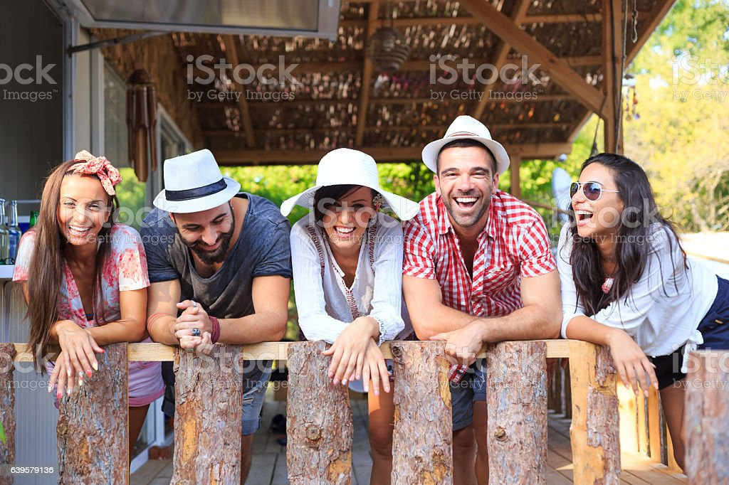 Group of friends relaxing and leaning on fence stock photo