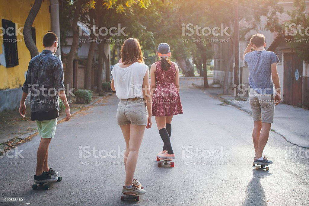 Group of friends riding on skateboards outdoors stock photo