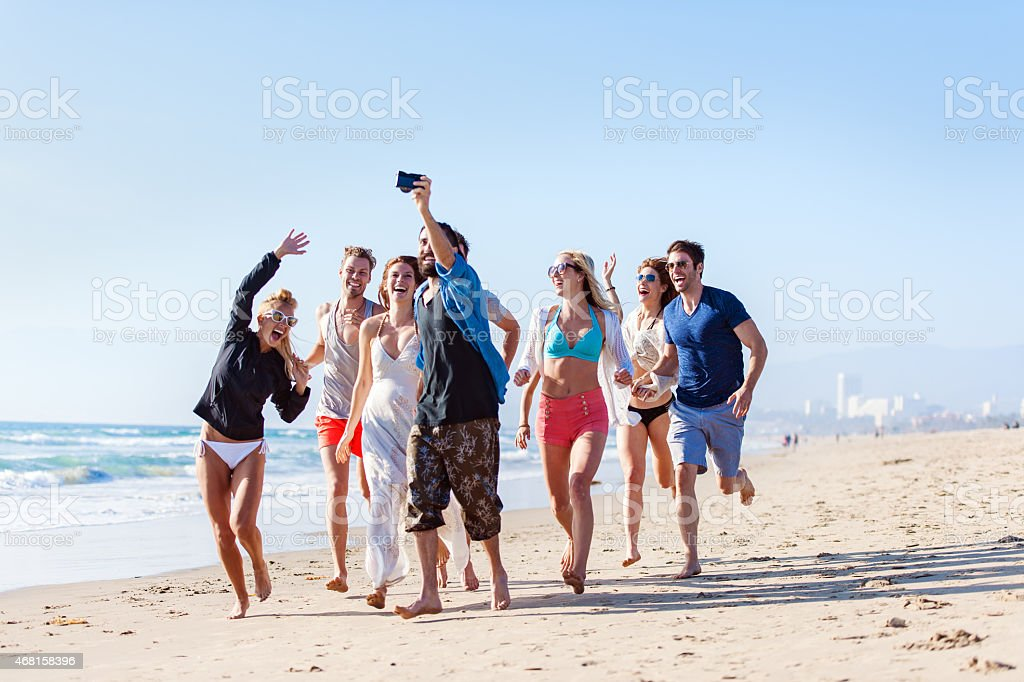 Group of friends running at the beach and filming stock photo