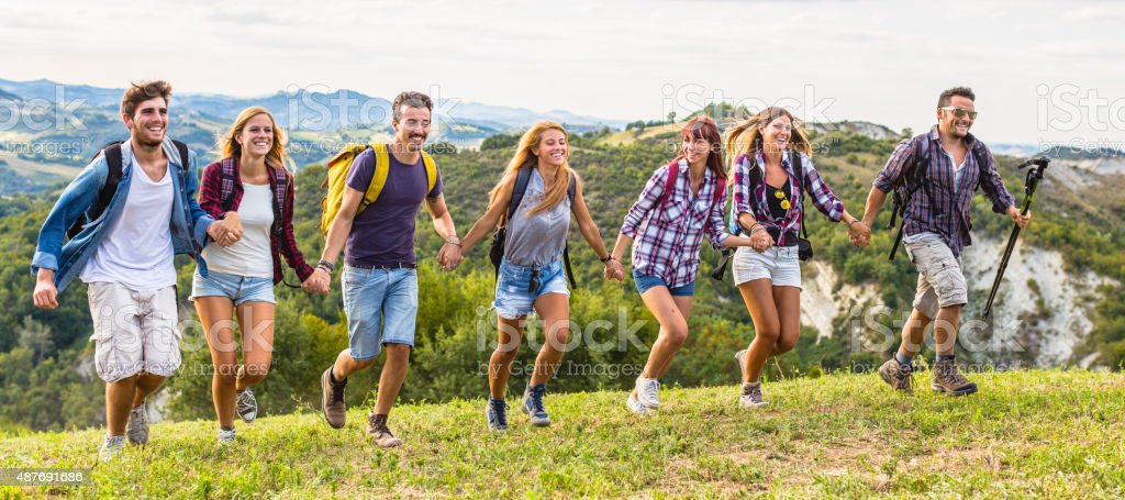 Group of friends running holding hands stock photo
