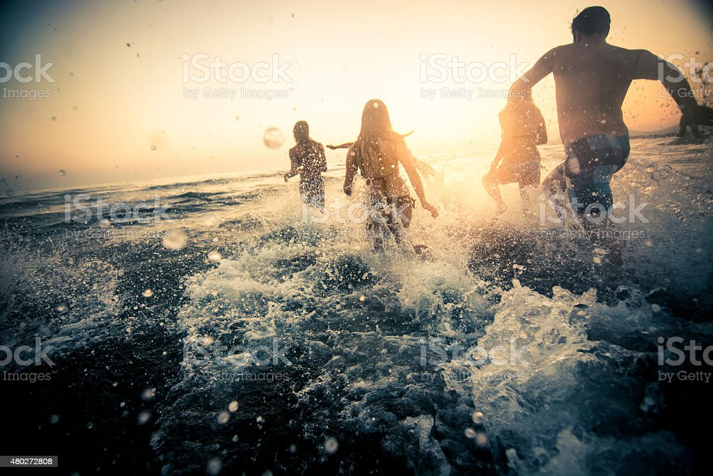Group of friends running into the water stock photo