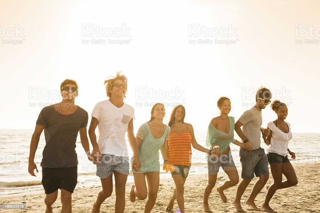 Group of friends running on the beach royalty-free stock photo