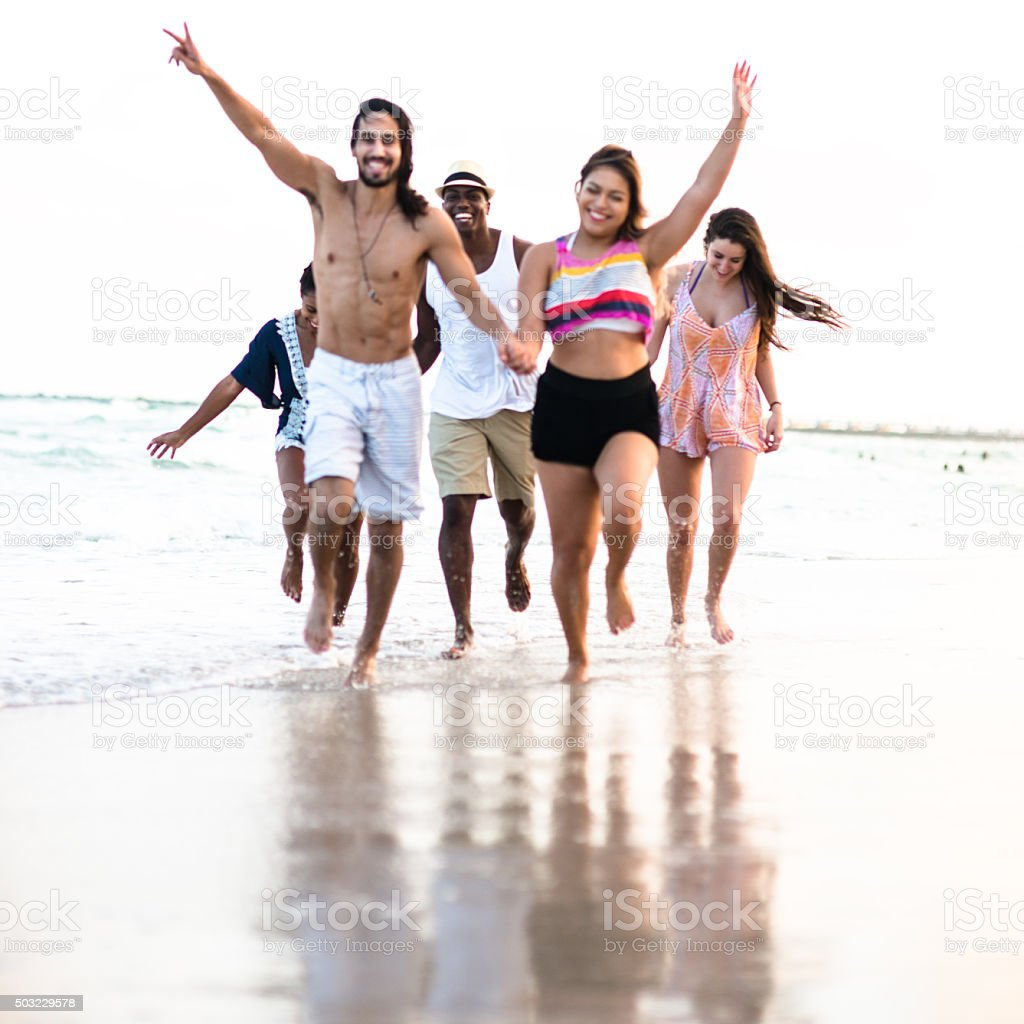 Group of friends running on the beach stock photo