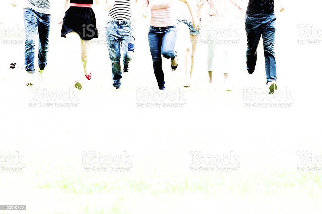 Group of friends running through the park royalty-free stock photo