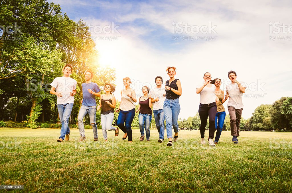 Group Of Friends Running Together At The Park stock photo