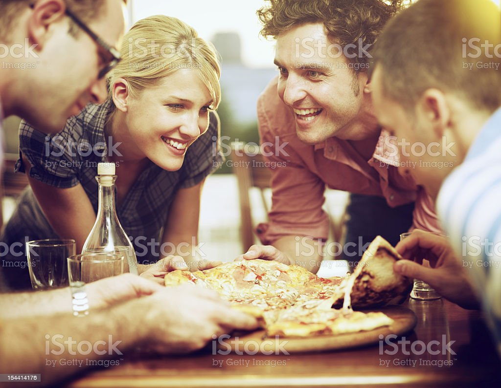 group of friends sharing a pizza stock photo