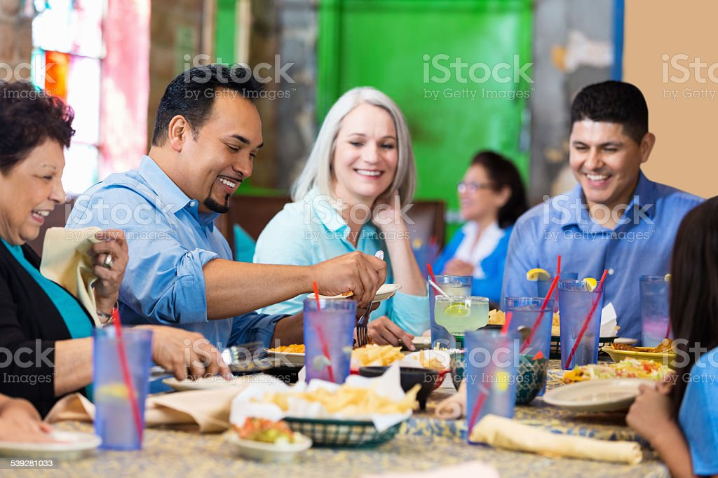 Group of friends sharing chips and salsa at Tex-Mex restaurant stock photo