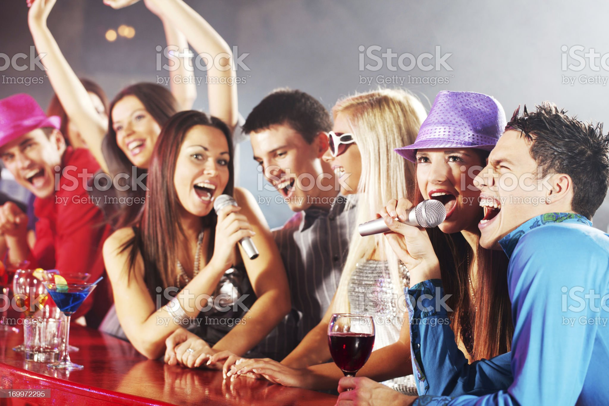 Group of friends singing at the bar counter. royalty-free stock photo