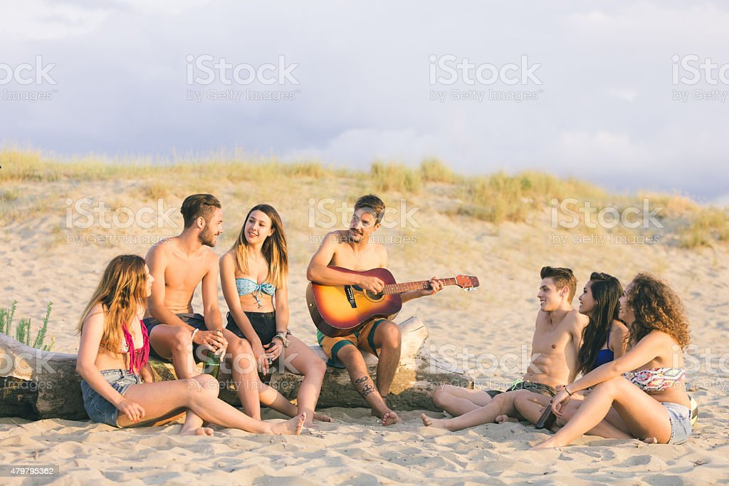 Group of friends singing on the beach at sunset. stock photo