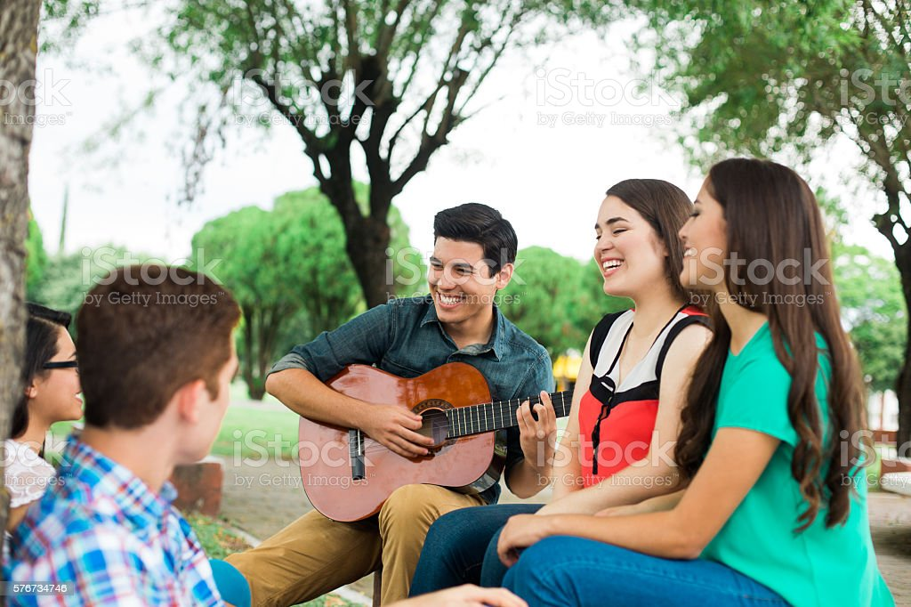 Group of friends sitting and listening to the guitar stock photo