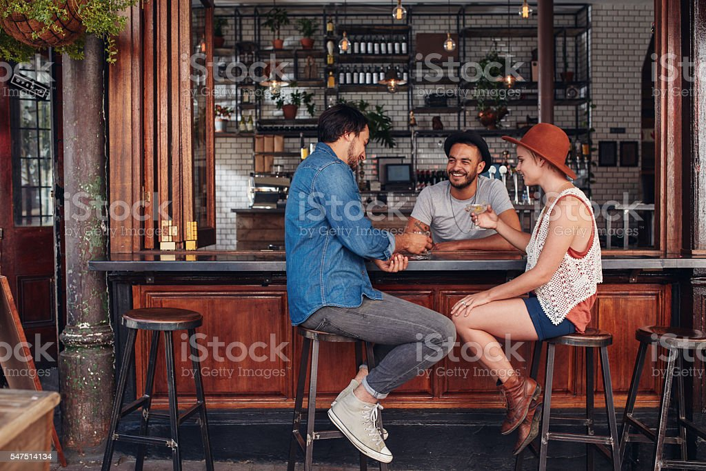 Group of friends sitting and talking at a cafe stock photo