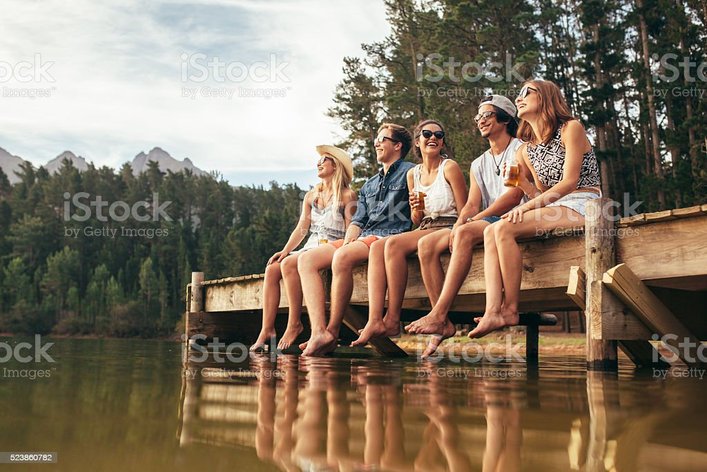 Group of friends sitting on jetty at lake stock photo