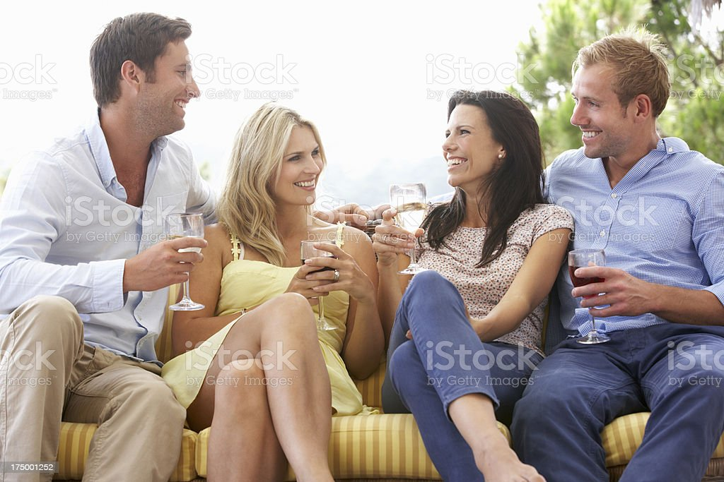 Group Of Friends Sitting On Outdoor Seat Together royalty-free stock photo