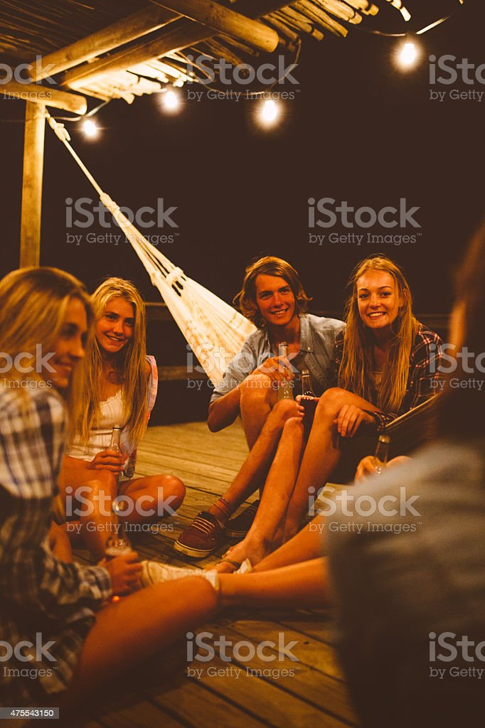 Group of friends sitting on porch at night stock photo