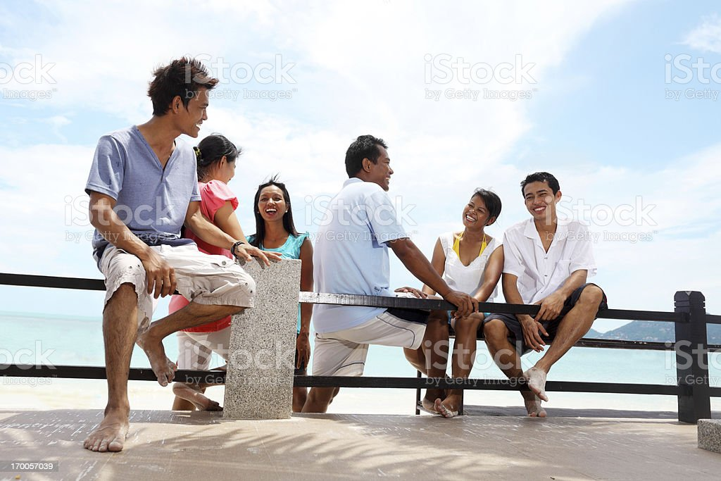 Group of friends sitting on the bench at beach. royalty-free stock photo