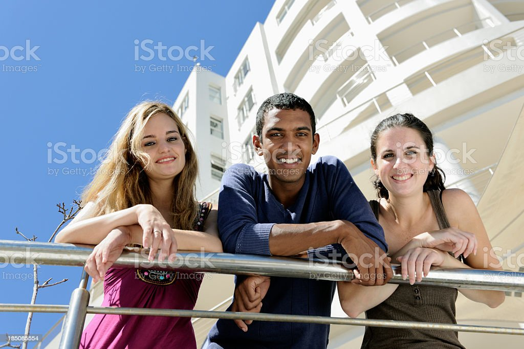 Group of friends smiling and leaning over silver railings stock photo