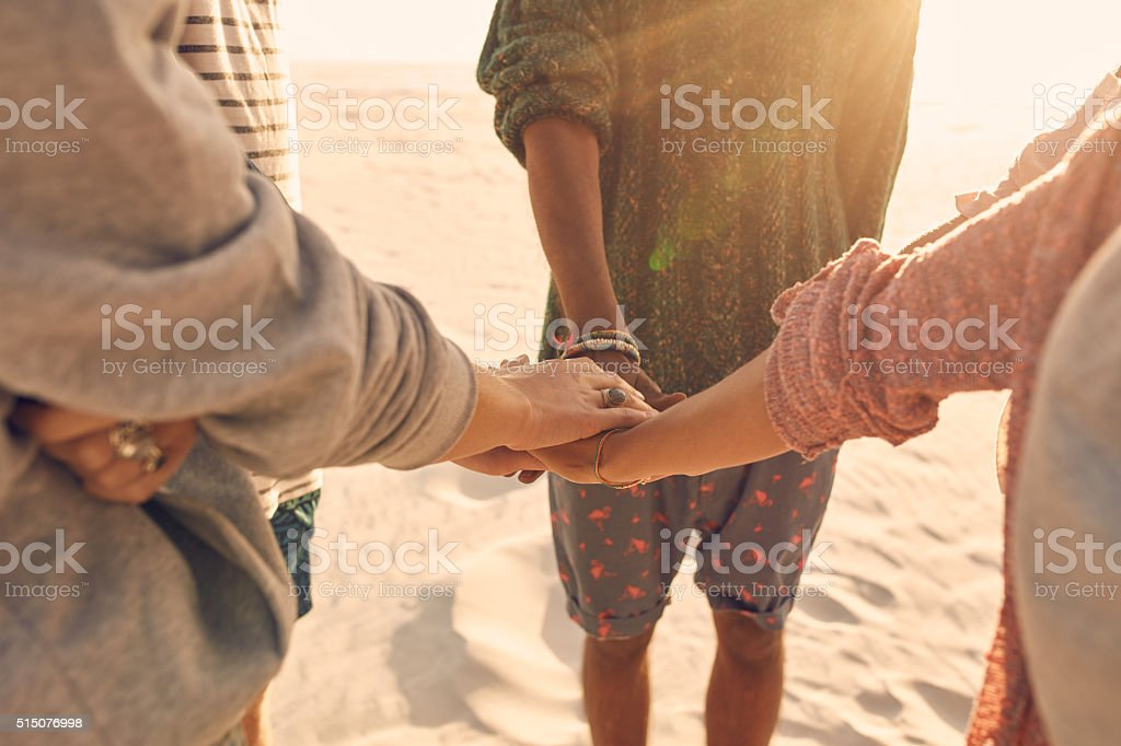 Group of friends stack their hands together stock photo