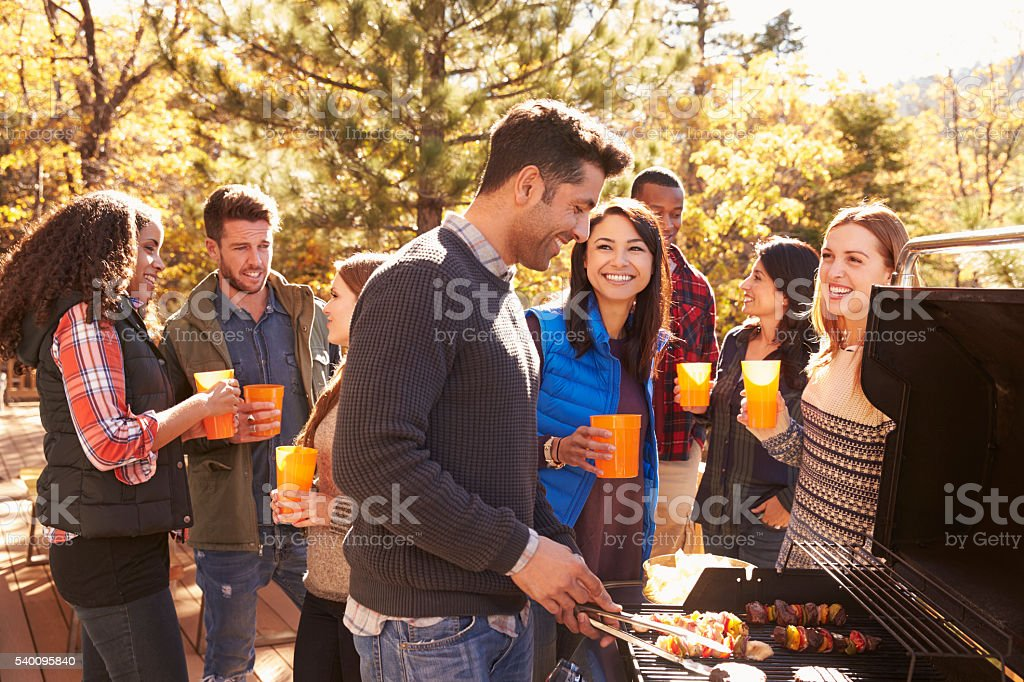 Group of friends stand at a barbecue, one cooking at grill stock photo