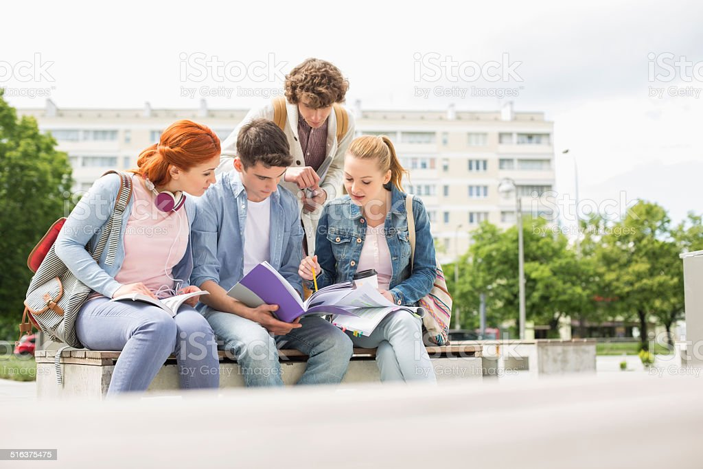 Group of friends studying together in university campus stock photo