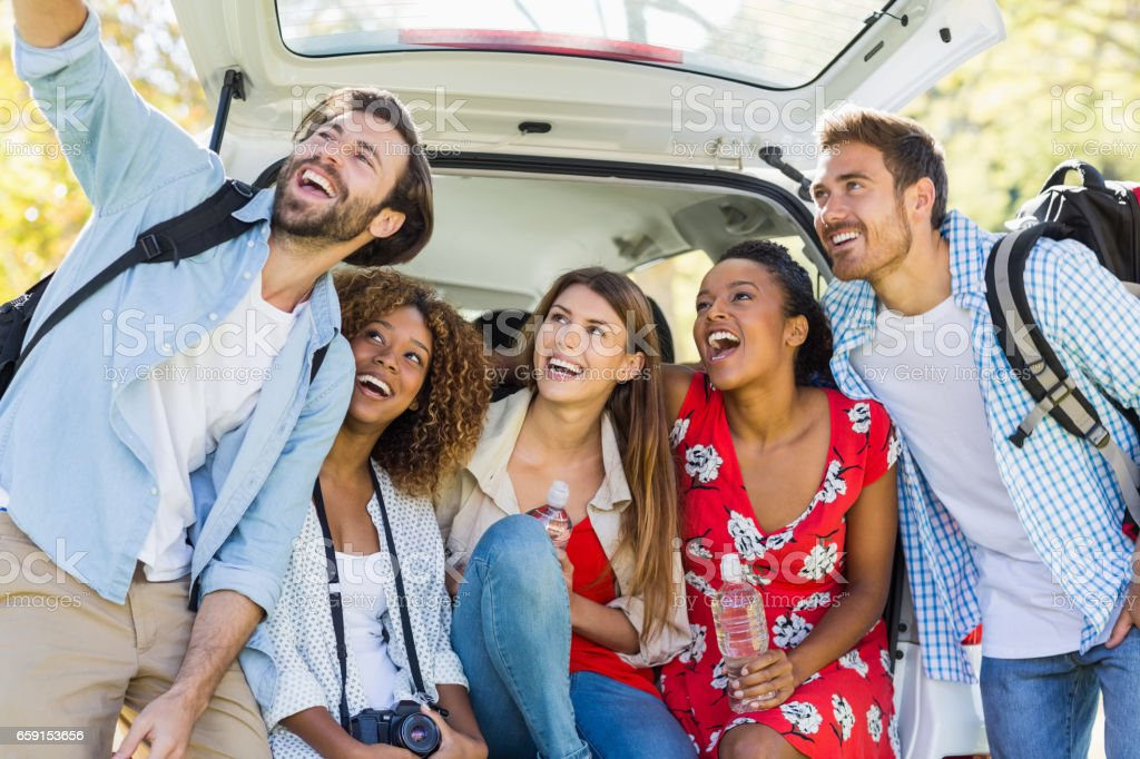 Group of happy friends taking a selfie from trunk of car