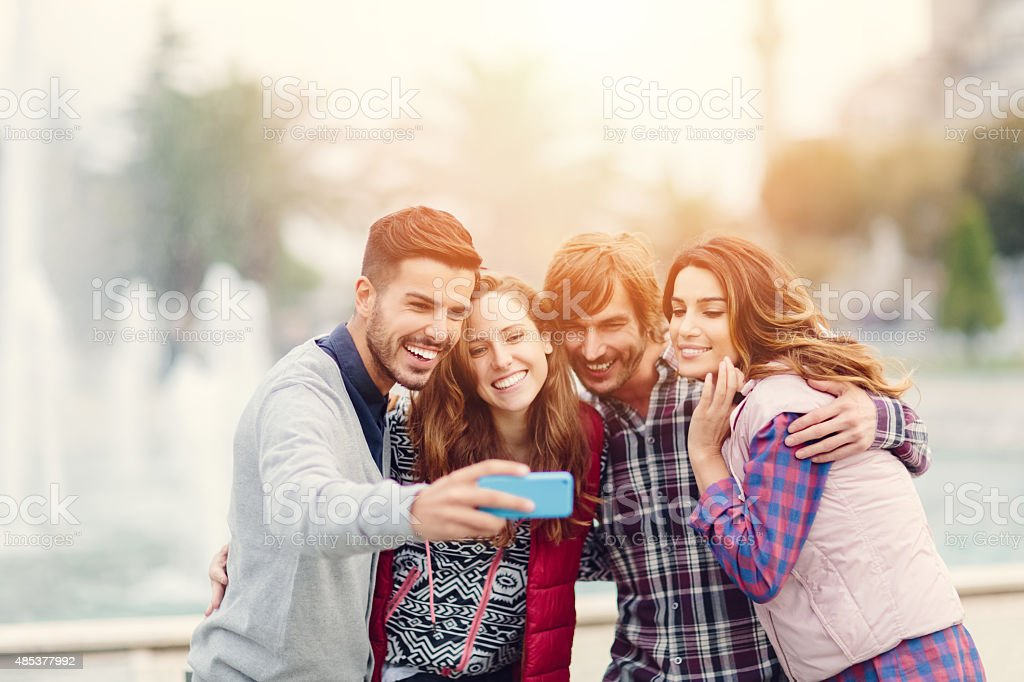 Group of friends taking a selfie with smartphone stock photo