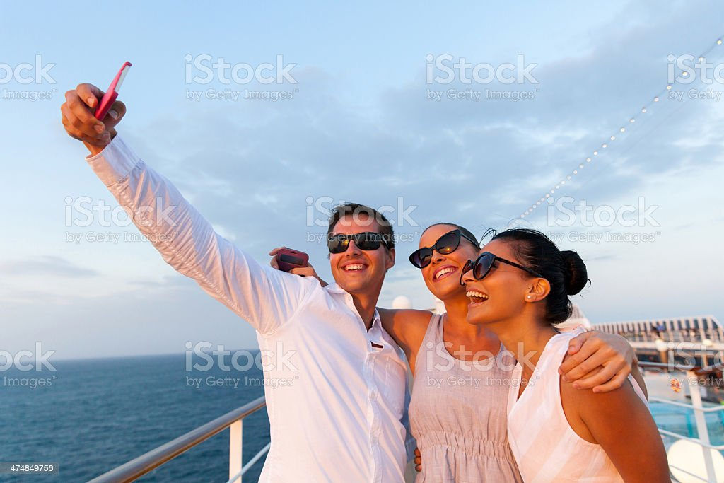 group of friends taking self portrait using smart phone stock photo