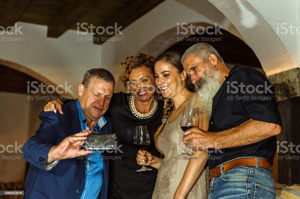 Group of Friends taking Selfie in Old Wine Cellar, Europe stock photo