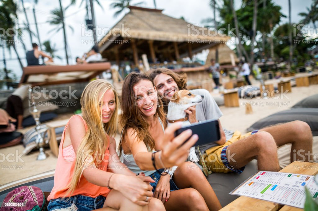 Group of friends taking selfies - two girls, one guy  and a cute dog with them at the beach cafe stock photo