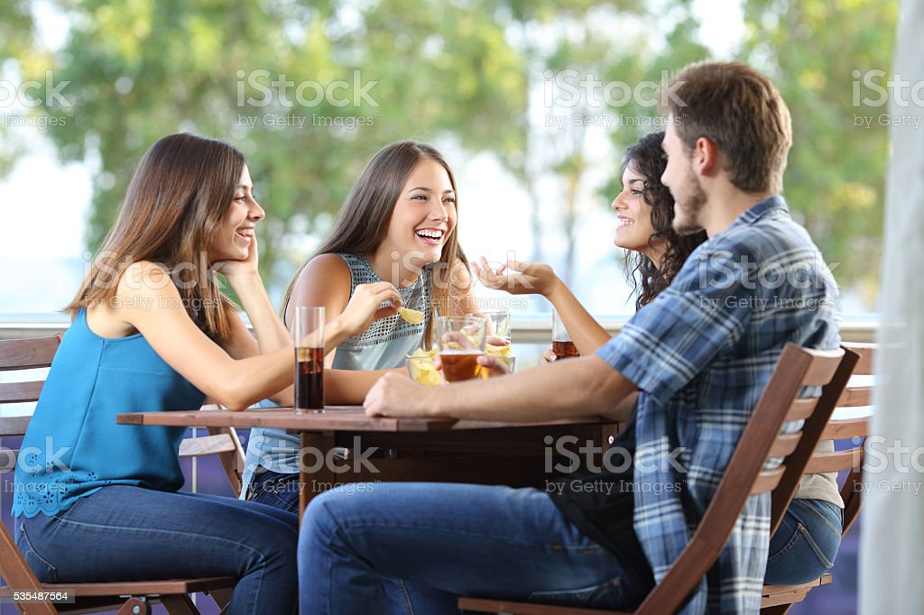 Group of friends talking and drinking at home stock photo