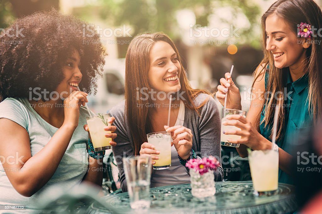 Group of friends talking and laughing in cafe stock photo