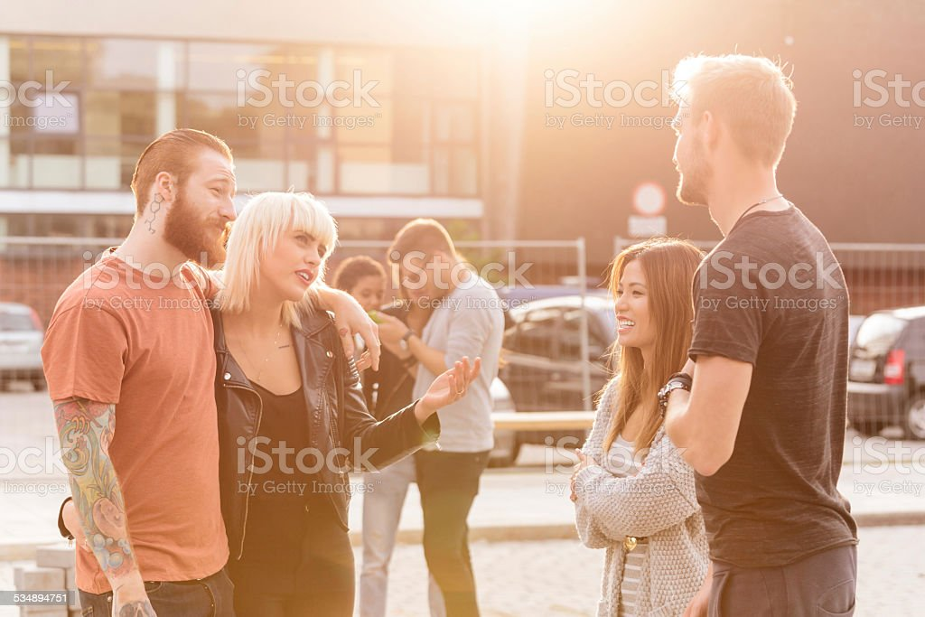 Group of friends talking outdoor stock photo