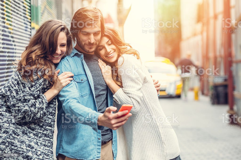 Group of friends texting on smartphone stock photo