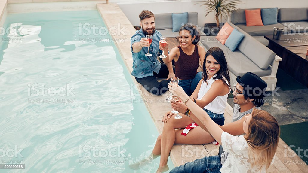 Group of friends toasting at pool party outdoor stock photo