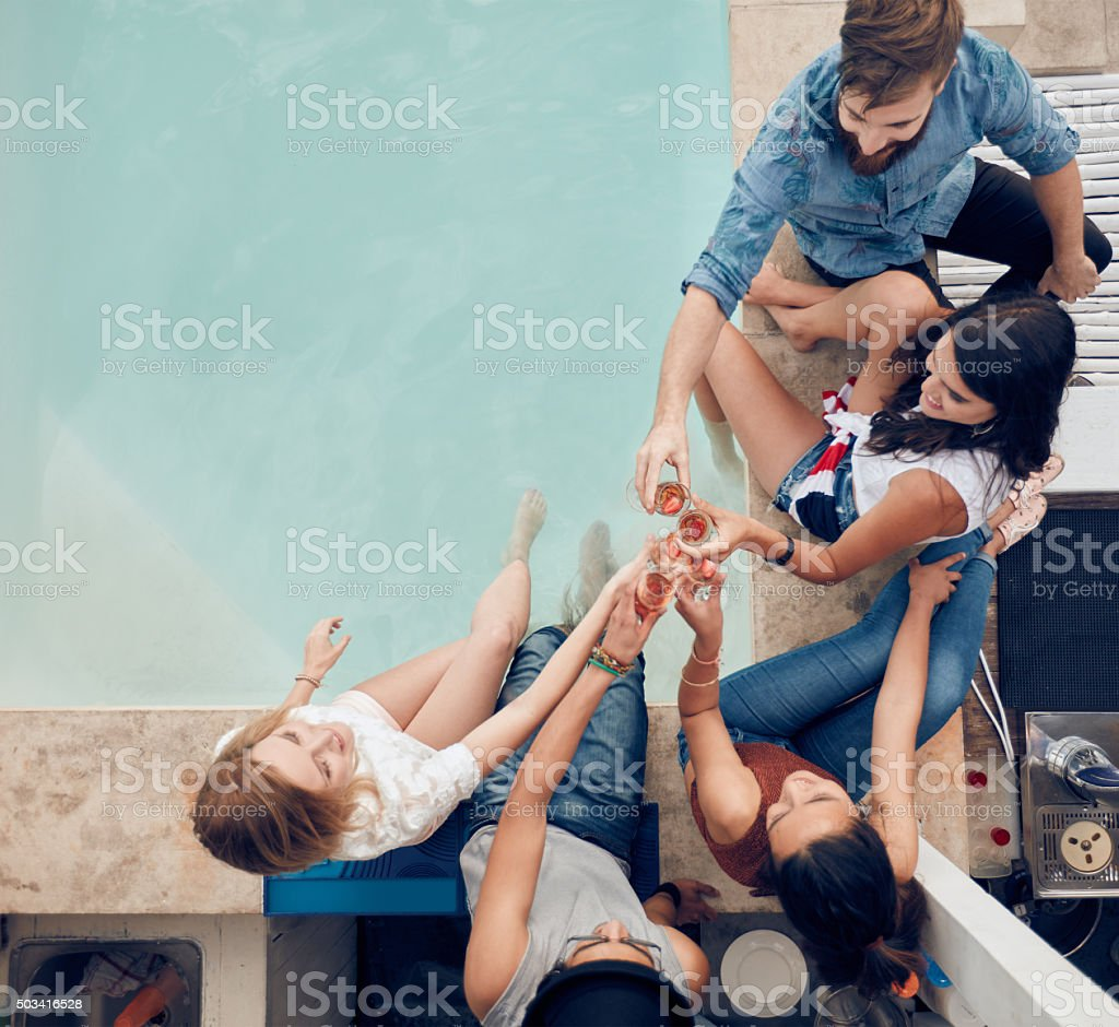 Group of friends toasting at poolside party stock photo