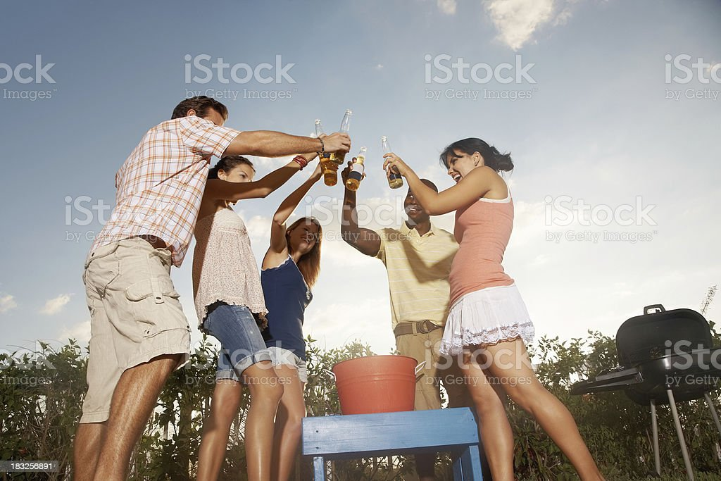 Group of friends toasting beer bottles on their vacation royalty-free stock photo