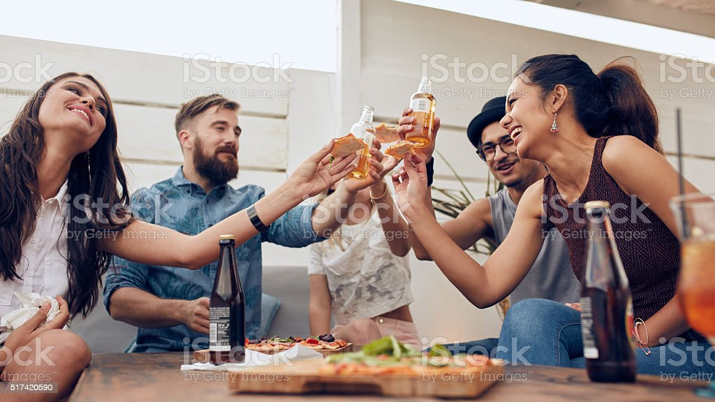 Group of friends toasting beers in a party stock photo