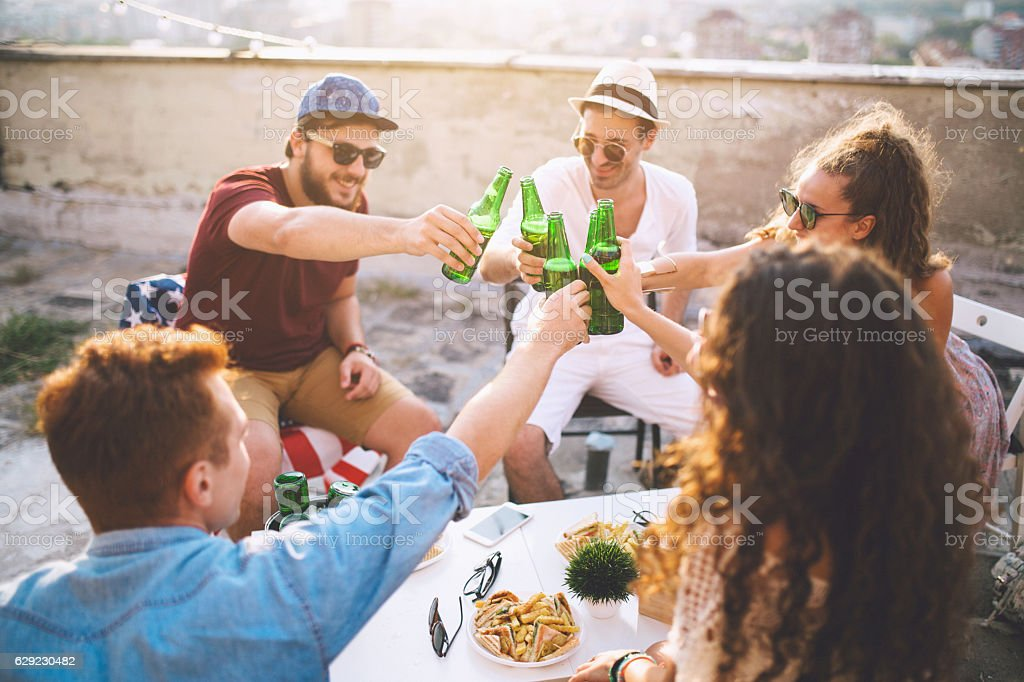 Group of friends toasting drinks outdoors stock photo