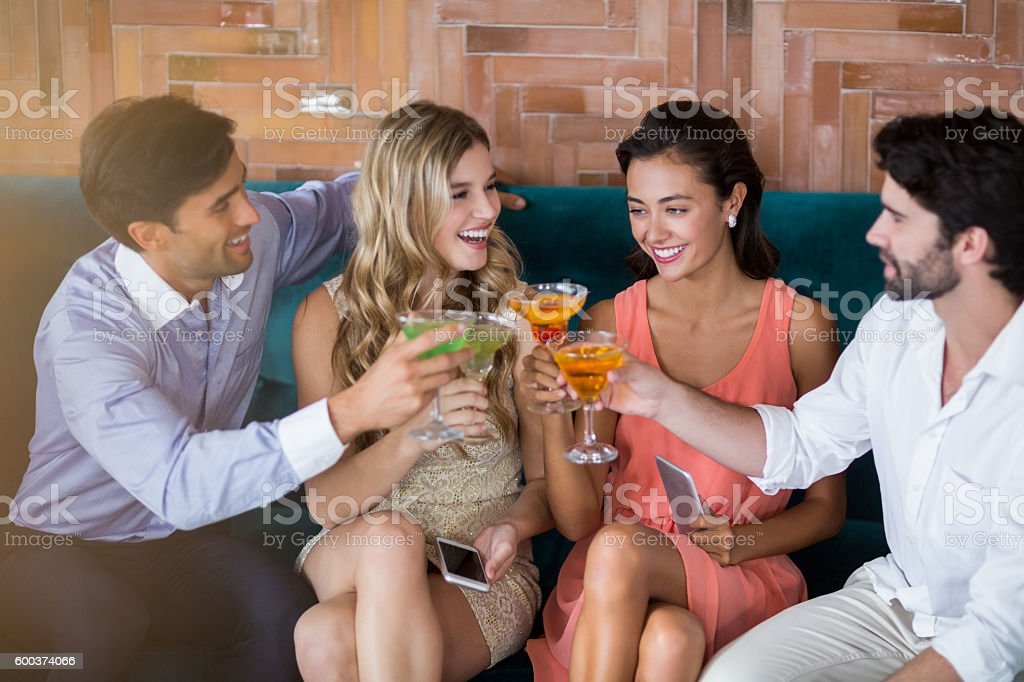 Group of friends toasting glasses of cocktail stock photo