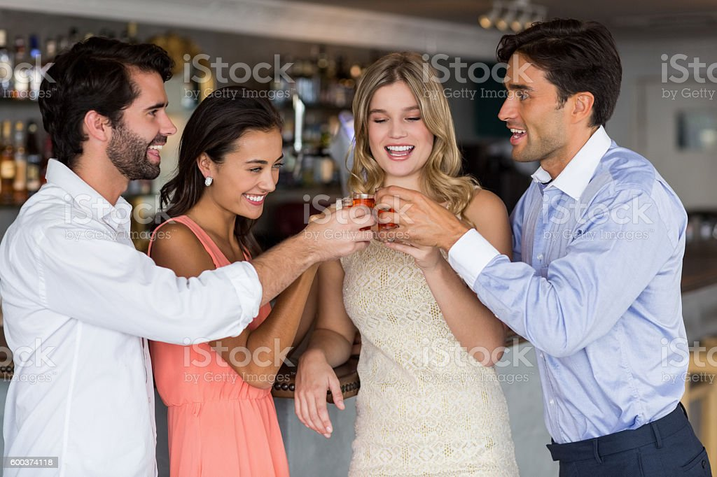 Group of friends toasting  glasses of tequila shot stock photo