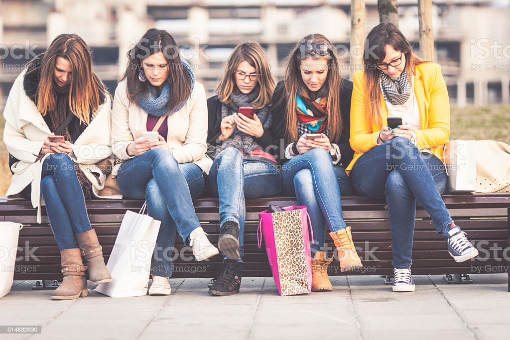 Group of friends using smart phones stock photo