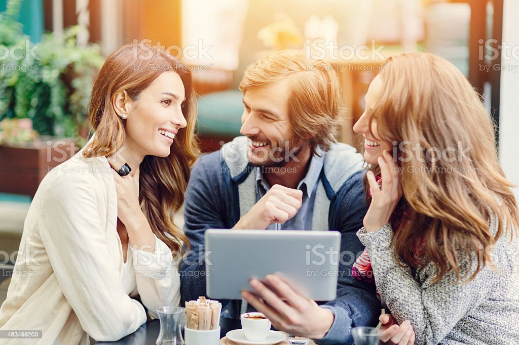 Group of friends using tablet at outdoors cafe stock photo