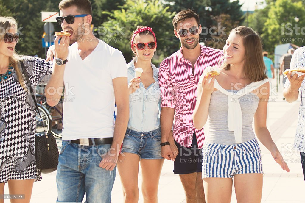 Group of friends walking and eating stock photo