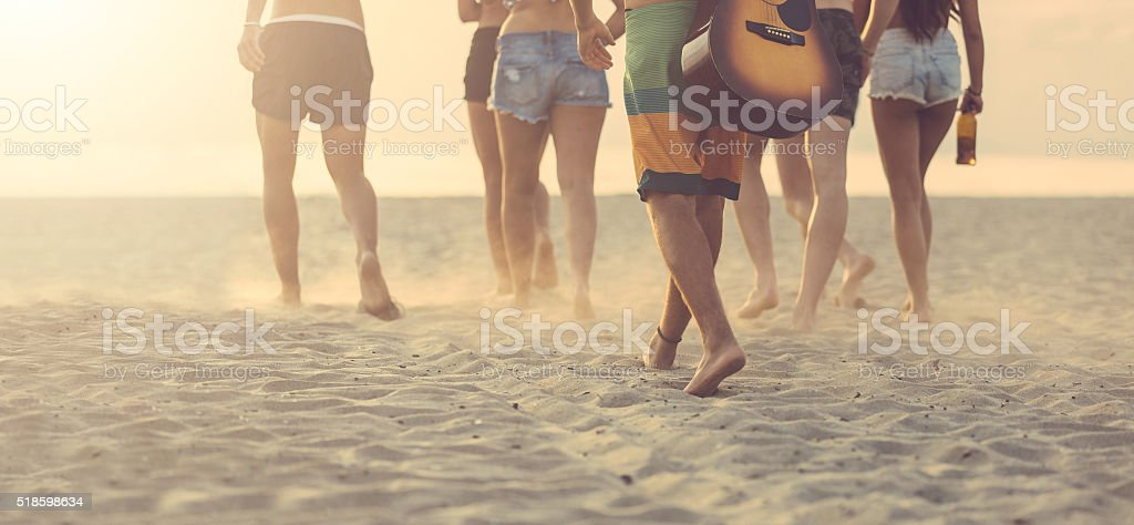 Group of friends walking on the beach at sunset. stock photo