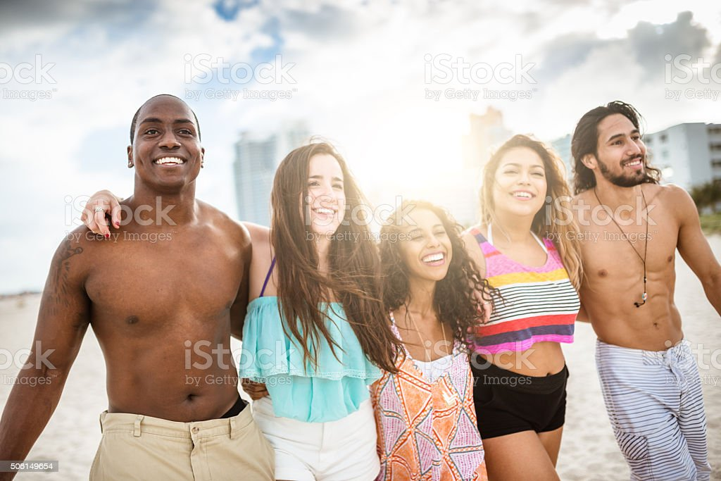 group of friends walking on the beach togetherness stock photo