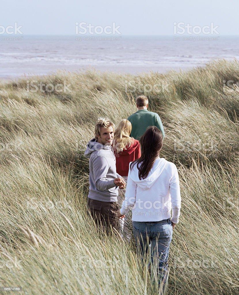 Group of friends walking towards ocean royalty-free stock photo