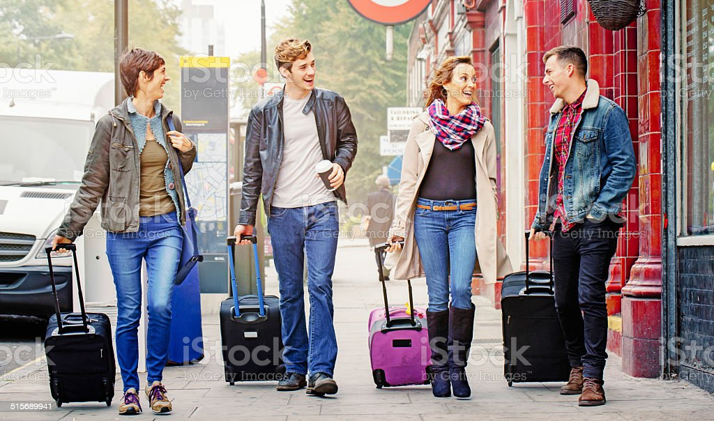 Group of friends walking with luggage stock photo