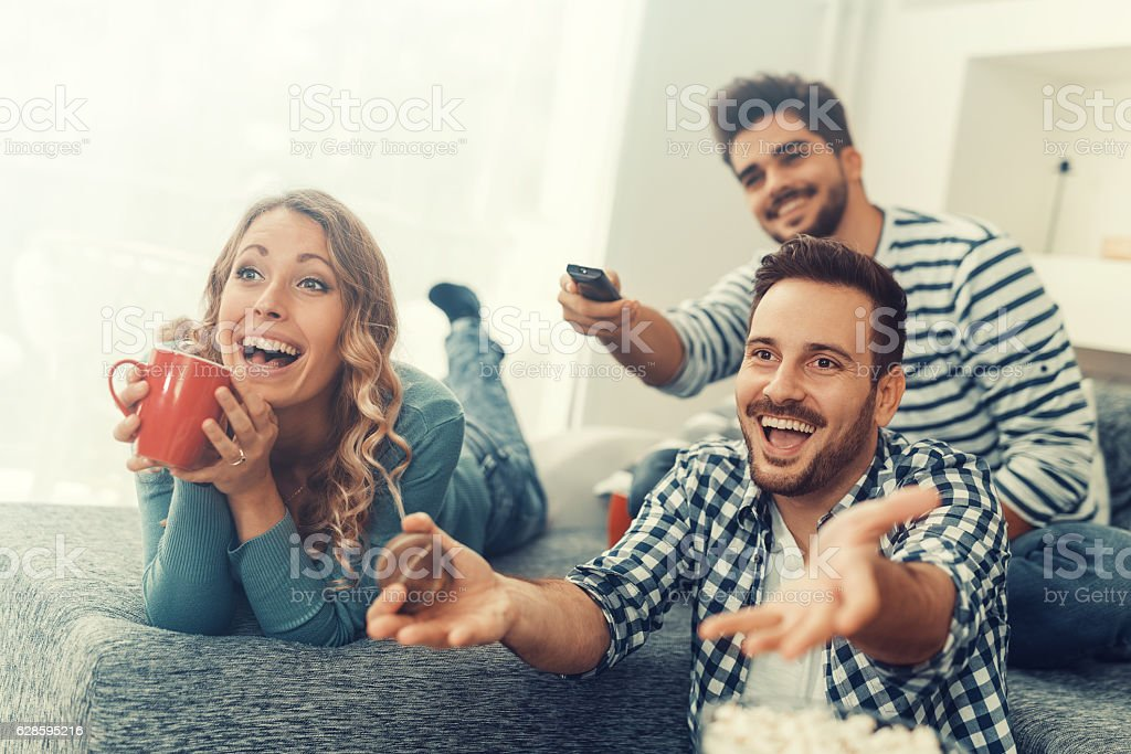 Group of friends watching TV at home stock photo