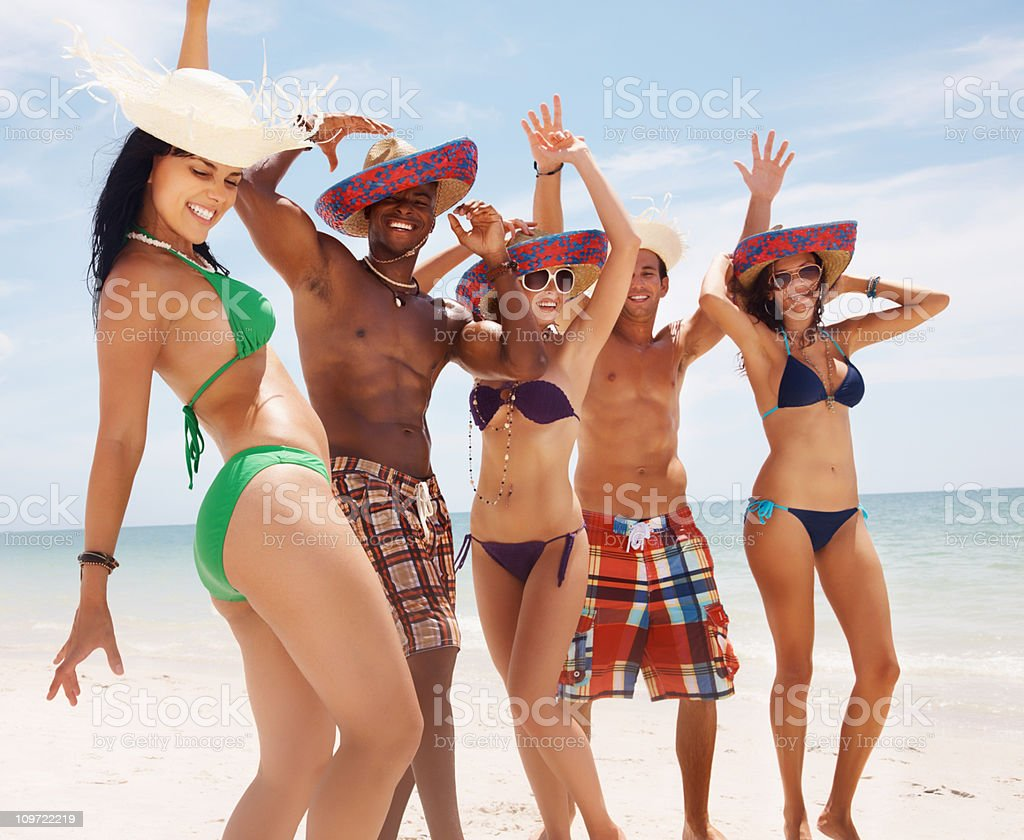 Group of friends wearing sunhat while dancing on beach royalty-free stock photo